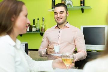 Bartender and smiling women at bar