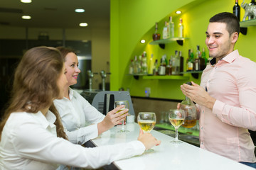 Bartender and smiling women at bar