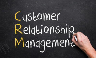hand writing customer relationship management on a chalk board