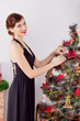 happy woman in evening dress red lipstick the Christmas tree