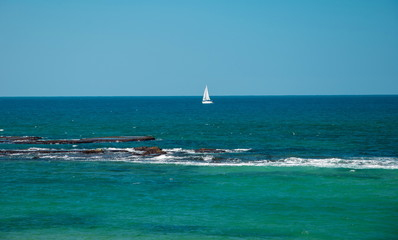 Seascape with a sailing boat on the horizon