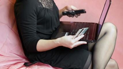 Woman with cell phone and PC on couch