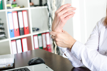 Businesswoman holding her painful wrist