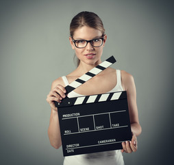 Media production. Pretty smiling female with clapperboard