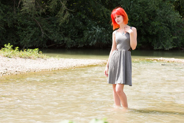 Pretty red hair girl walking in river