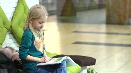 Little blonde girl reading a book while waiting her mom