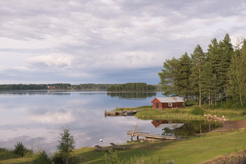 Summer in Sweden - traditional red Cottage at a lake