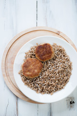 Buckwheat with meat cutlets, above view, vertical shot