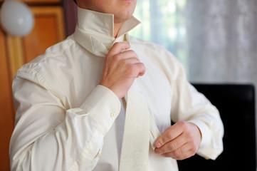 groom to tie a tie