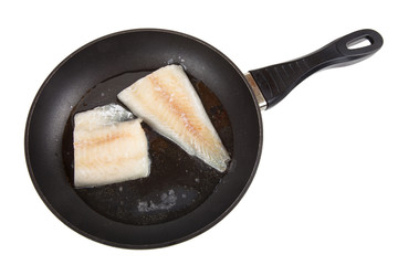 Hake fillets in the pan. Isolated on white background