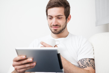 Man using tablet pc during breakfast