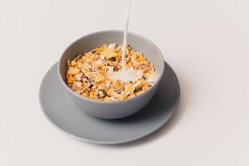 Muesli bowl with milk stream. Vintage style.