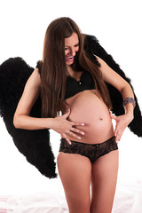 beautiful pregnant woman with black wings in surprise