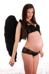 beautiful pregnant woman with black wings standing