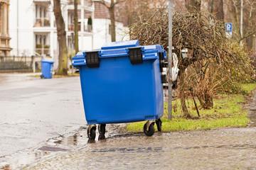 Ein blauer Müllcontainer aus Kunststoff steht am Strassenrand