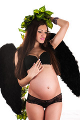 attractive pregnant woman with black wings with foliage on head