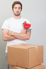 Close-up of young man while he is packing a cardboard box