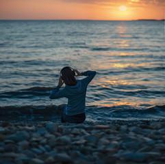 Woman in headphones sitting on beach on sunset