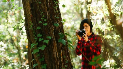 Hipster girl taking photo in the forest
