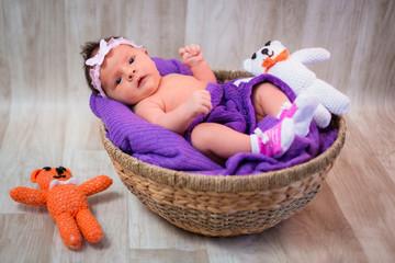 Newborn baby girl in a round wicker basket
