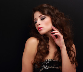 Beautiful woman with chic brown curly hair looking on black