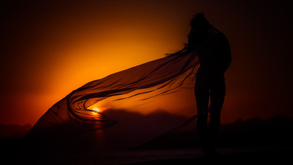 Silhouette of the girl on the sunset