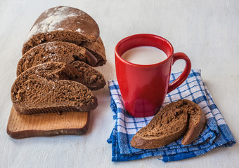 Sliced rye bread Tabatiere on a cutting board and  red cup with