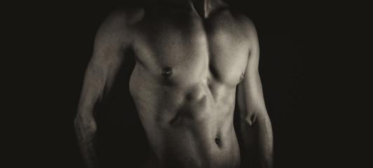 Unrecognizable muscular male body. Black and white.