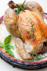 baked chicken on a platter with herbs