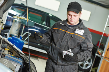 mechanic checking oil level in automobile