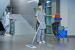 worker cleaning floor with machine - 74860633