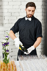 Waiter bartender pouring wine at party