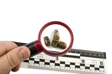 bullets and shell under a magnifying glass with a line of forens