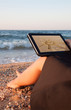 young girl and her tablet with sun picture on beach