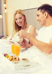 smiling couple having breakfast in bed in hotel