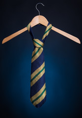 Fashionable men's tie on a hanger. On a blue background.