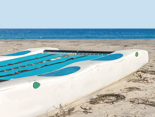 Close up rear view, beached white and blue kayak on the sand