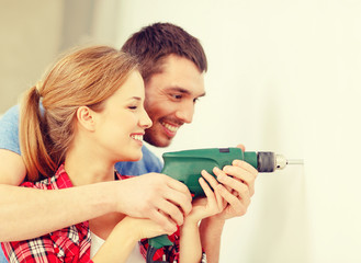 smiling couple drilling hole in wall at home