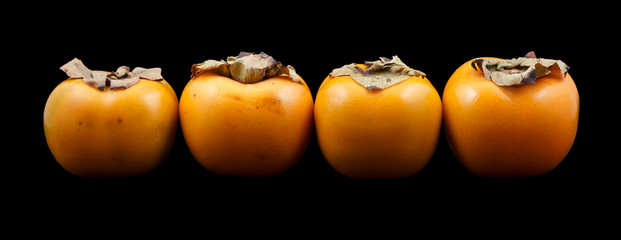Four persimmon fruits isolated against a black background