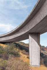 Rural area,under curving freeway overpass.Blue sky and clouds