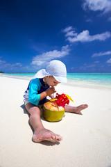 Boy drinking coconut water on tropical island beach with blue la
