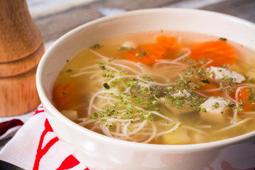Chicken broth with vermicelli, vegetables and herbs, closeup