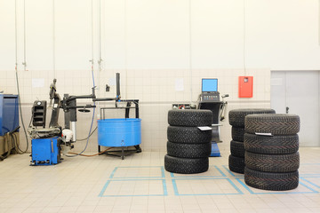 The image of tyre fitting machine and the sets of wheels