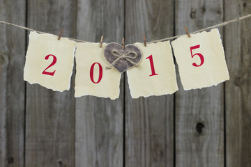 Year 2015 on antique paper with heart hanging on clothesline