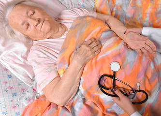 Female caretaker checking pulse of old woman