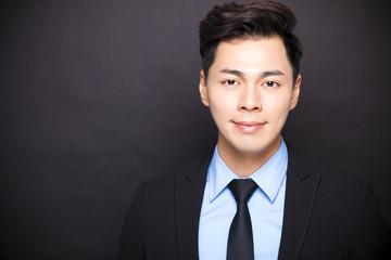 Smiling businessman standing before black background