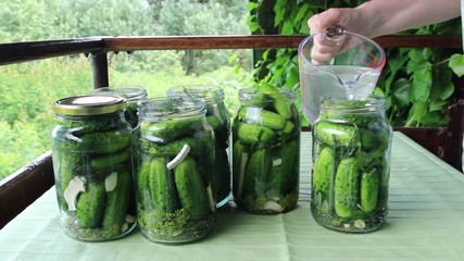 Preserves for winter. Woman cover cucumbers with salt water.