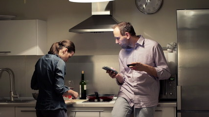 Happy couple talking and using smartphone while cooking