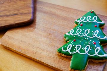 Christmas tree cookie on wood plate.