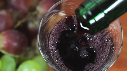 Red Wine Pouring Into A Glass. Grapes in background.